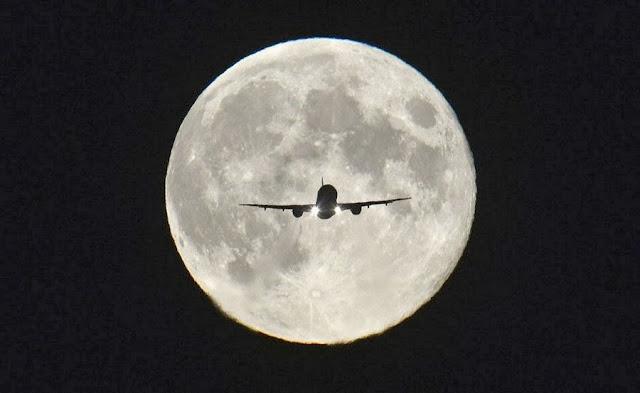 Пассажирский самолет заходит на посадку в лондонском аэропорту «Хитроу» во время полнолуния