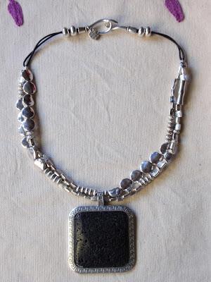 collar-gargantilla artesanal elaborado con abalorios plateados de distintos tipos y colgante de piedra de lava volcanica