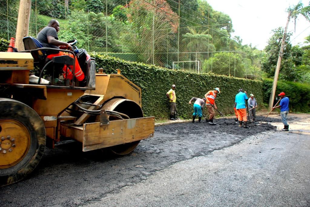 Nove homens da Secretaria Municipal de Obras e Serviços Públicos trabalham na pavimentação da Rua José Arthur Josetti, na entrada da localidade