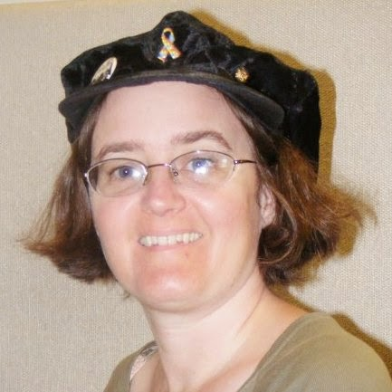 "Cynthia Parkhill wearing black hat decorated with button displaying two sour-faced critics who ask, ""But is it art?"", Toastmasters International lapel pin and a cloissone Autism Awareness pin"