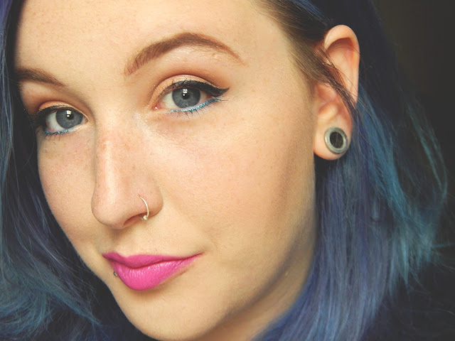 girl with winged eyeliner and bright pink lipstick