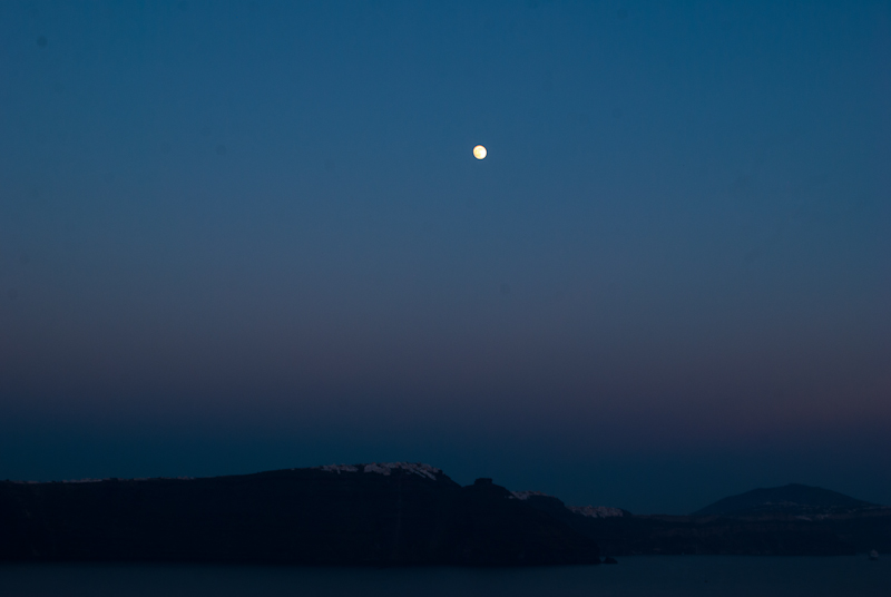 image of the moon in the sky of oia santorini