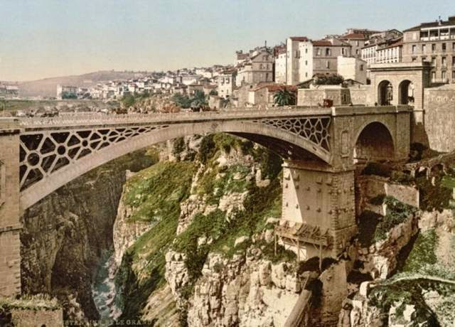 "Constantine, Algeria, has the nickname ""the city of bridges"" for a reason: it's full of them. This is just one of the many bridges that range from massive stone feats, to treacherously narrow plank bridges. This image dates from the late 19th century, but this bridge still stands, and there's another, smaller one underneath it."