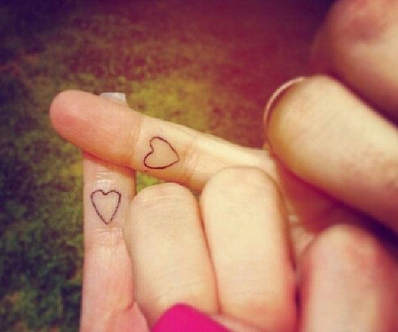 dos dedos cruzados con tatuajes de corazones pequeños