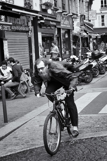Shot in Paris - a street photograph of a cyclist with long hair