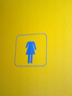 En la puerta del baño de señoras, el icono que representa a la mujer no tiene cabeza