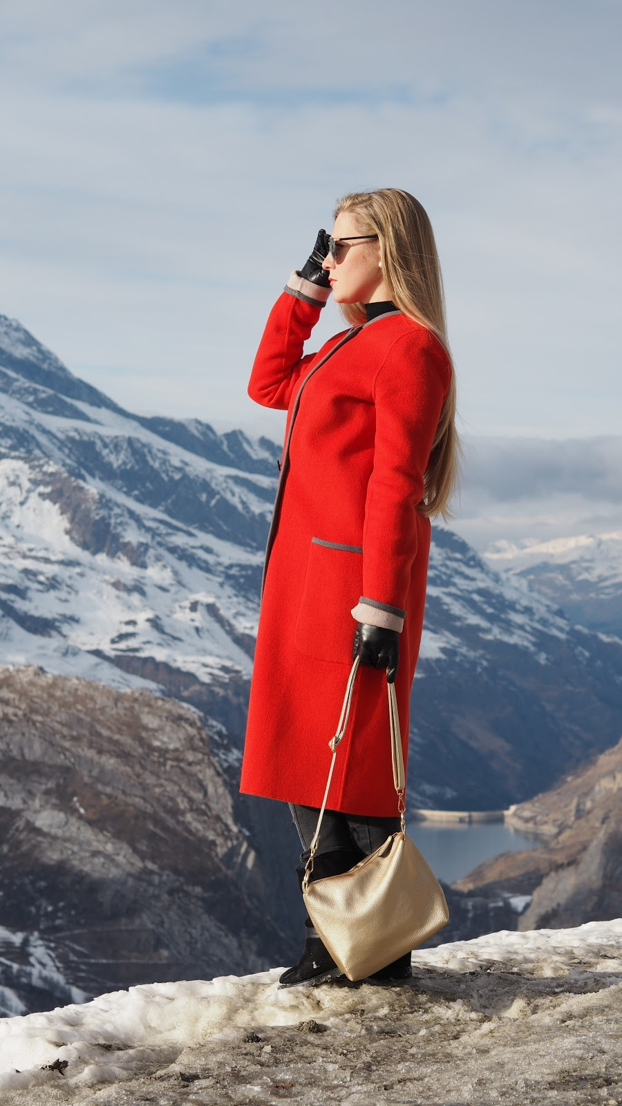 Blonde Girl wearing red coat in the Snow Capped Mountains, Val d'Isere, France
