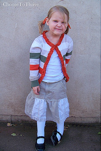 little girl in khaki skirt and red and green ruffle sweater