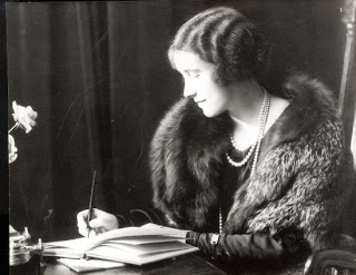 The Queen Mother in a fur stole writing a  letter.