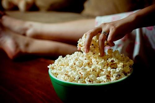no sofá comendo pipoca e assistindo filme