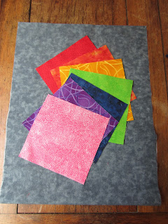 rainbow fabric squares laid out on grey backing fabric