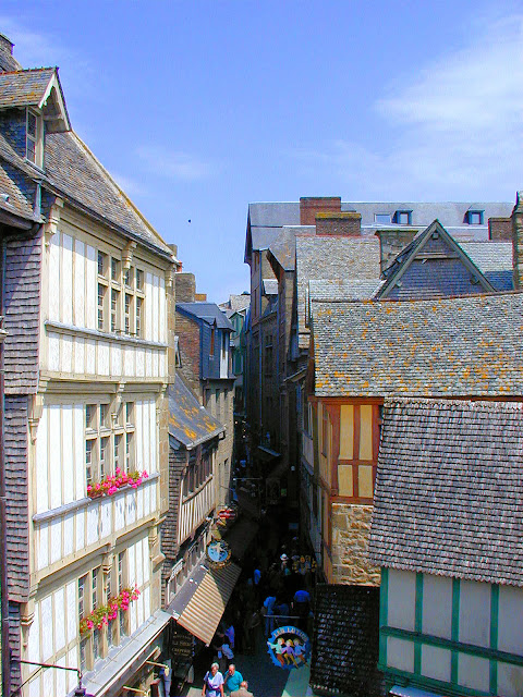 Storied half-timbered architecture lines the streets in the medieval village at the base of Mont Saint-Michel. Photo: WikiMedia.org.