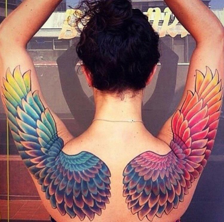 mujer de espaldas, lleva tatuada la esplda con tatuaje de alas multicolores