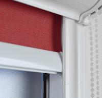 Czerwona roleta okienna z białą prowadnicą