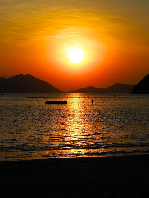 Gold, red and orange of the sunset over the ocean at Repulse Bay Beach, Hong Kong