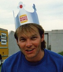 a blonde man wearing a burger king crown