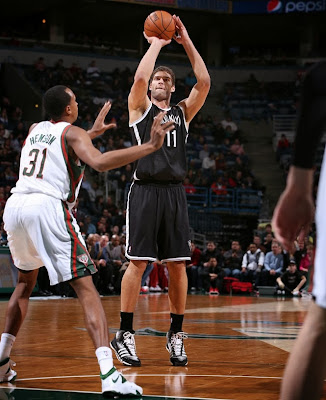 Nets' Brook Lopez takes a shot over Bucks' John Henson