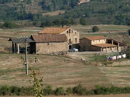 El conjunt d'edificacions de La Muntada amb la masia, la masoveria i el paller, vist des de la Costa de Montoliu
