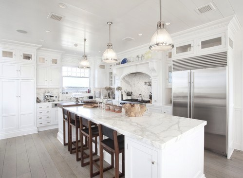 kitchen with island with marble counter top and white cabinets, bar seats, wood floors and three pendant lights