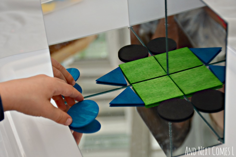 Exploring symmetry using wooden shapes in a mirror box from And Next Comes L