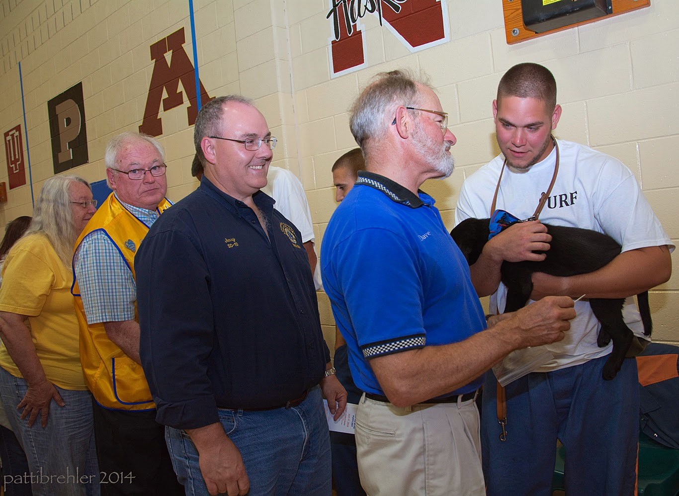 One woman and three men are standing in line, talking to the prisoners that are standing against the wall in the gym. The inmate on the right is wearing blue pants and a white t-shirt. He is holding a small black lab puppy and leaning toward another man and listening. The woman, wearing a yellow shirt, is on the far left, followed by a man wearing a yellow vest, then a man wearing blue jeans and a blue shirt, then a bearded man wearing khakis and a royal blue shirt.