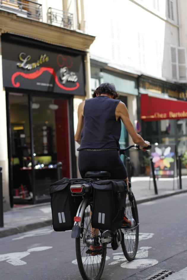 streetstyle - woman on bike riding through city street in Paris