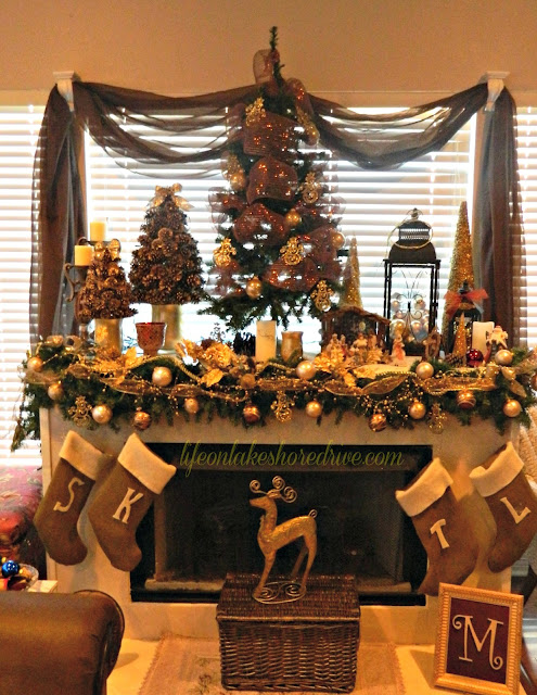 "alt=""Christmas mantel with pine cone trees and burlap stockings"""