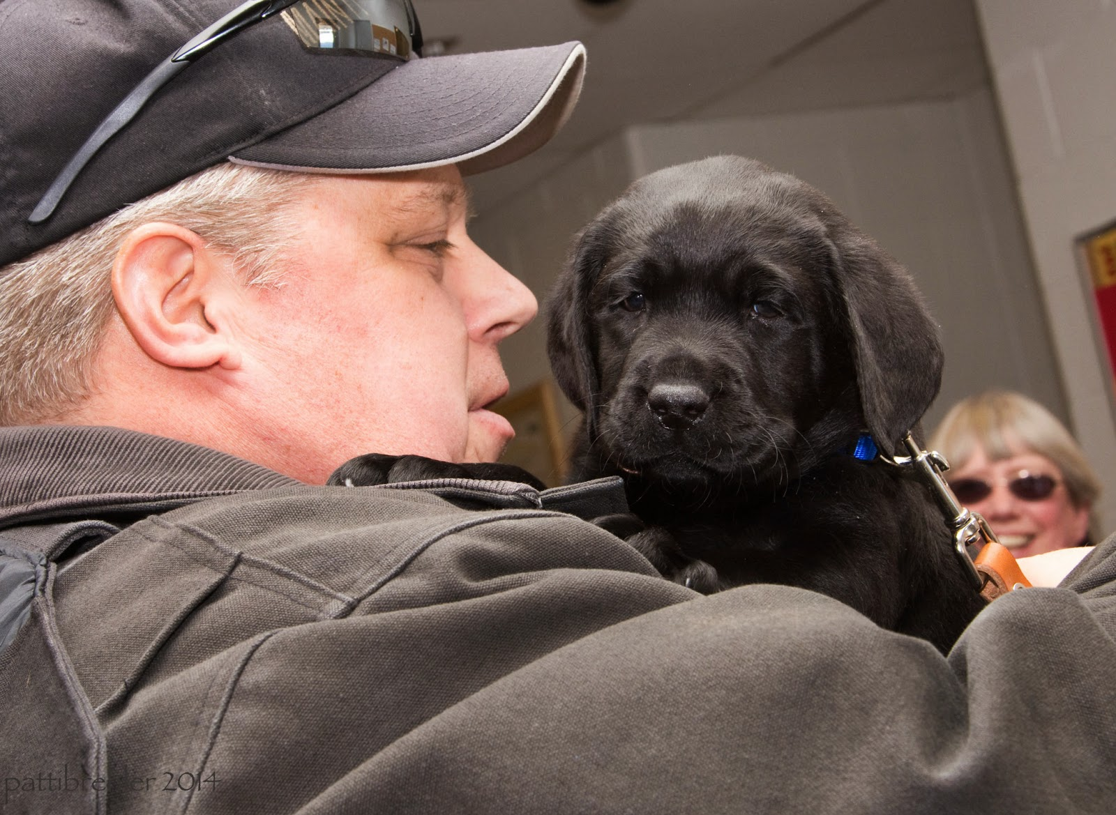 Now the black lab puppy is being held by a different man. The man is facing to the right, he is wearing a black jacket and a black baseball cap with sunglasses resting on the brim. The puppy is in his arms and is looking right at the camera. In the background is the smiling face of a woman with white hair and sunglasses.
