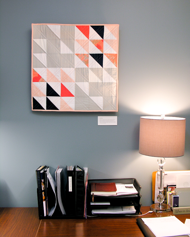 Little Pieces coral and navy modern wall quilt living in its Wheaton College home   by Lovely and Enough