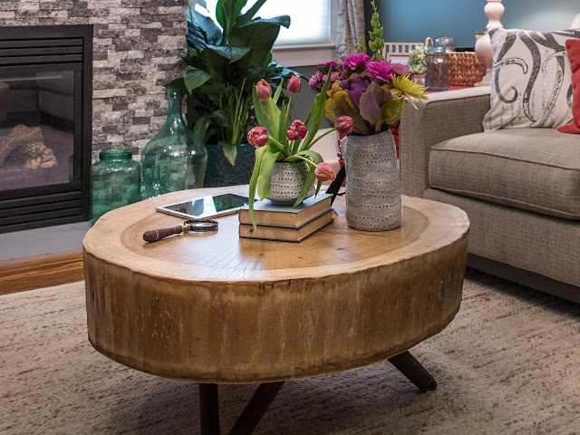 a dark brown wood tree stump coffee table with two hand made vases on top