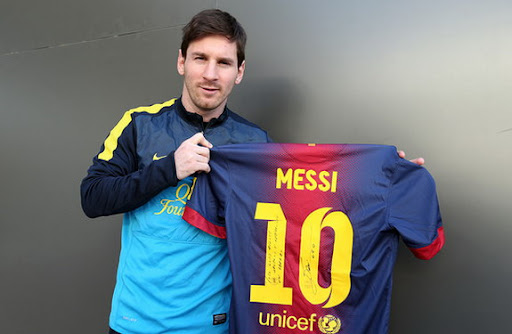 Barcelona player Lionel Messi poses with a shirt he would send to Bayern Munich legend Gerd Müller