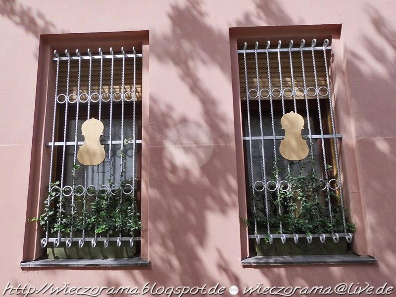 Das Foto zeigt zwei Fenster eines Geigenbauers im Hochpaterre mit Gittern geschuetzt in die jeweils eine Geige kunstvoll eingearbeitet wurde Ausserdem einige schmuckvolle Gruenranken