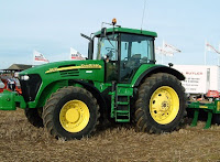 Picture of a green John Deere tractor with yellow wheel hubs and black tyres, and a enclosed cab.