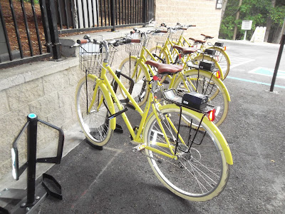 Yellow bikes attached to bikeshare docking stations off Water Street in Ashland, Oregon