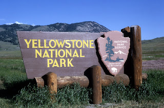 large wooden sign at the entrance of park stating Yellowstone National Park