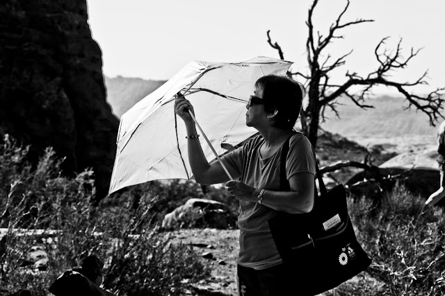 A tourist exploring Arches National Park with a sun umbrella.