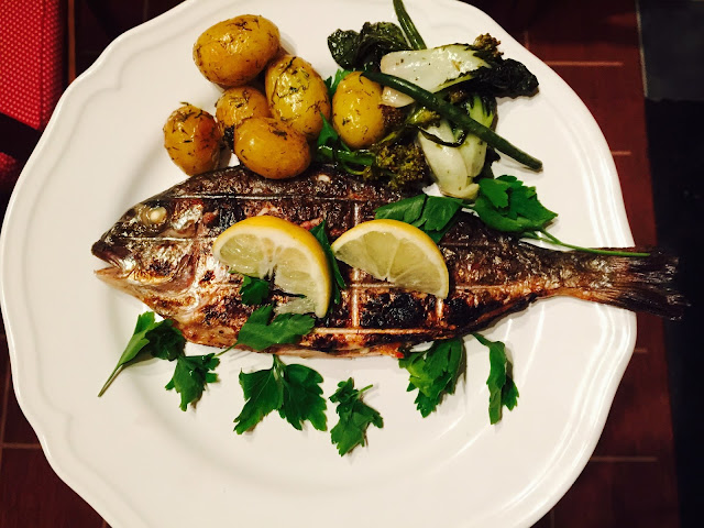 Plate of new potatoes and barbecued stuffed Greek sea bream with greens