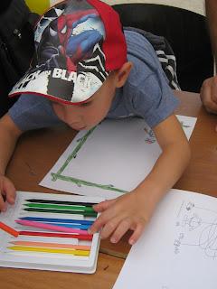 Spiderman-es sapkás kisfiú keresztül hajol az asztalon, hogy színt válasszon magának.