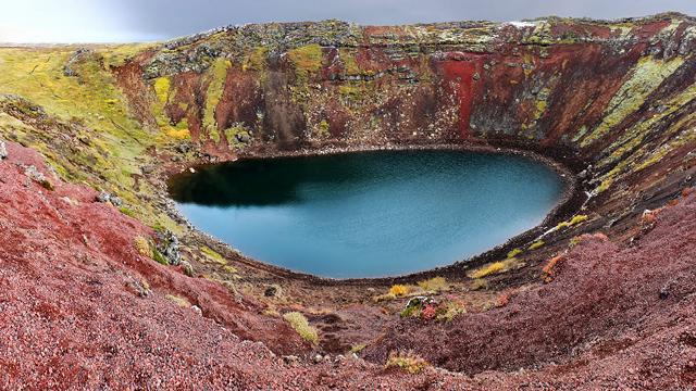 lago circular - água de cor verde - cercado de rochas de cor verde e vermelho escuro