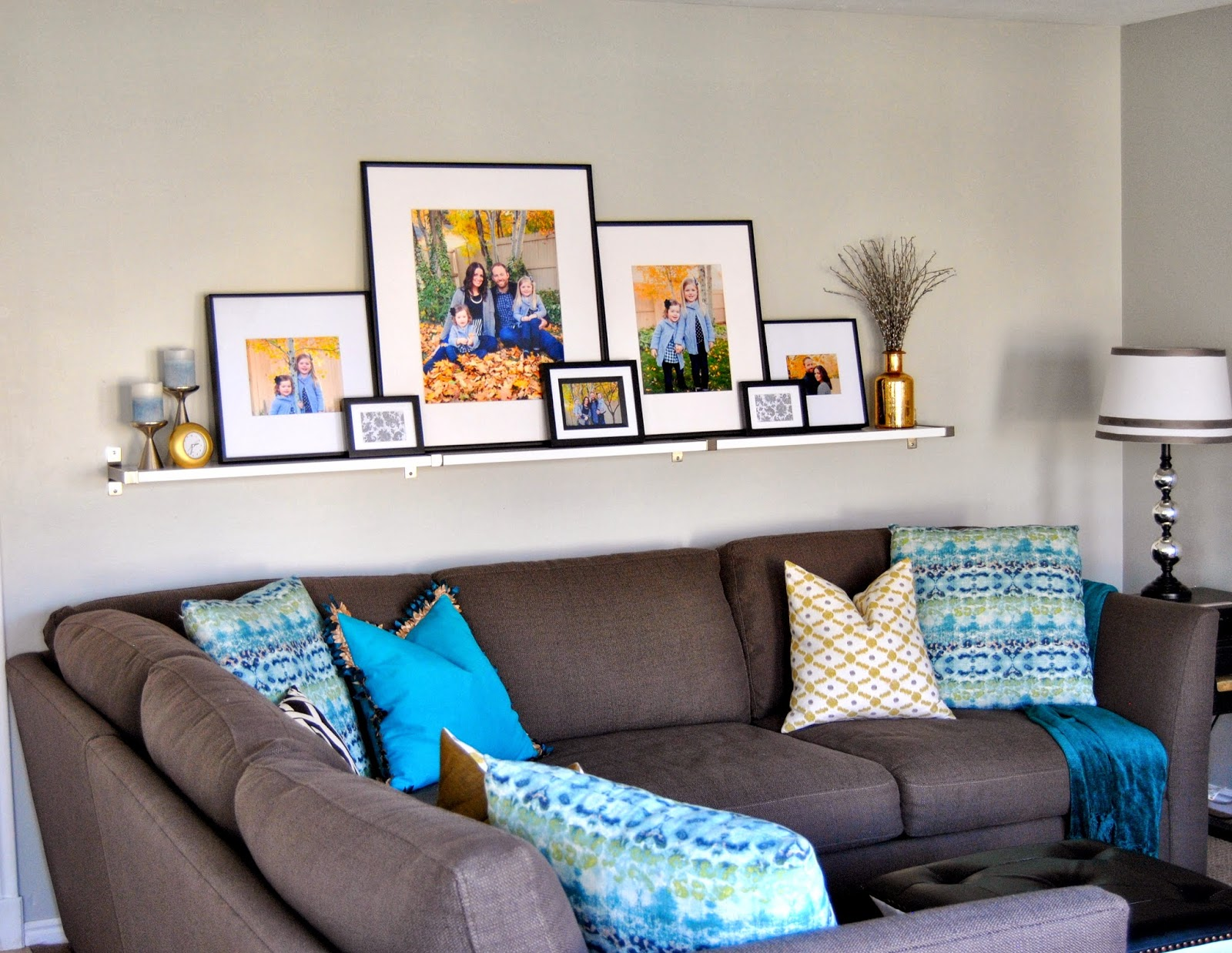 turquoise, gray paint, white shelf, black and white, gallery wall, silver and gold, sectional, custom pillows, diy, low cost decorating