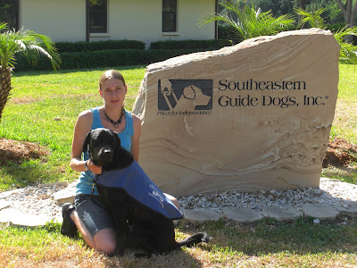 Picture of Rudy & I beside the guide dog sign - he's in coat