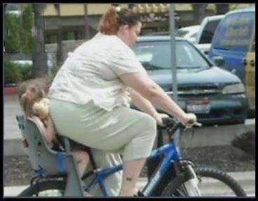 Mujer obesa en una bicicleta con un bebe en la parte posterior.