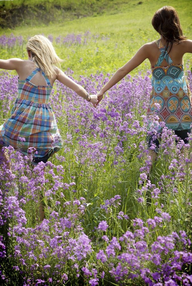 girls-holding-hands-flower-field-2.jpg
