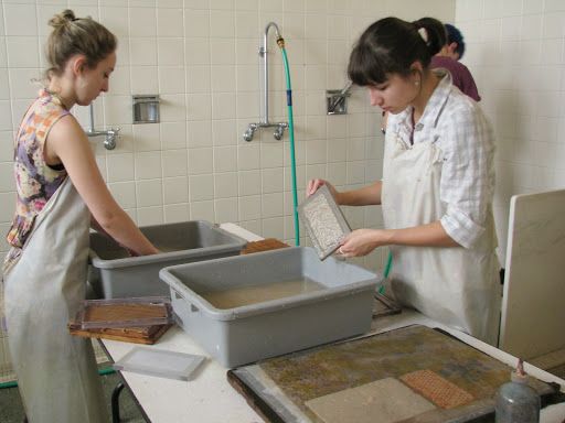 Two students mold paper