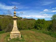 La Creu-Pedró de Sant Andreu de Gurb amb el mas El Puig al seu darrere i al fons de la imatge