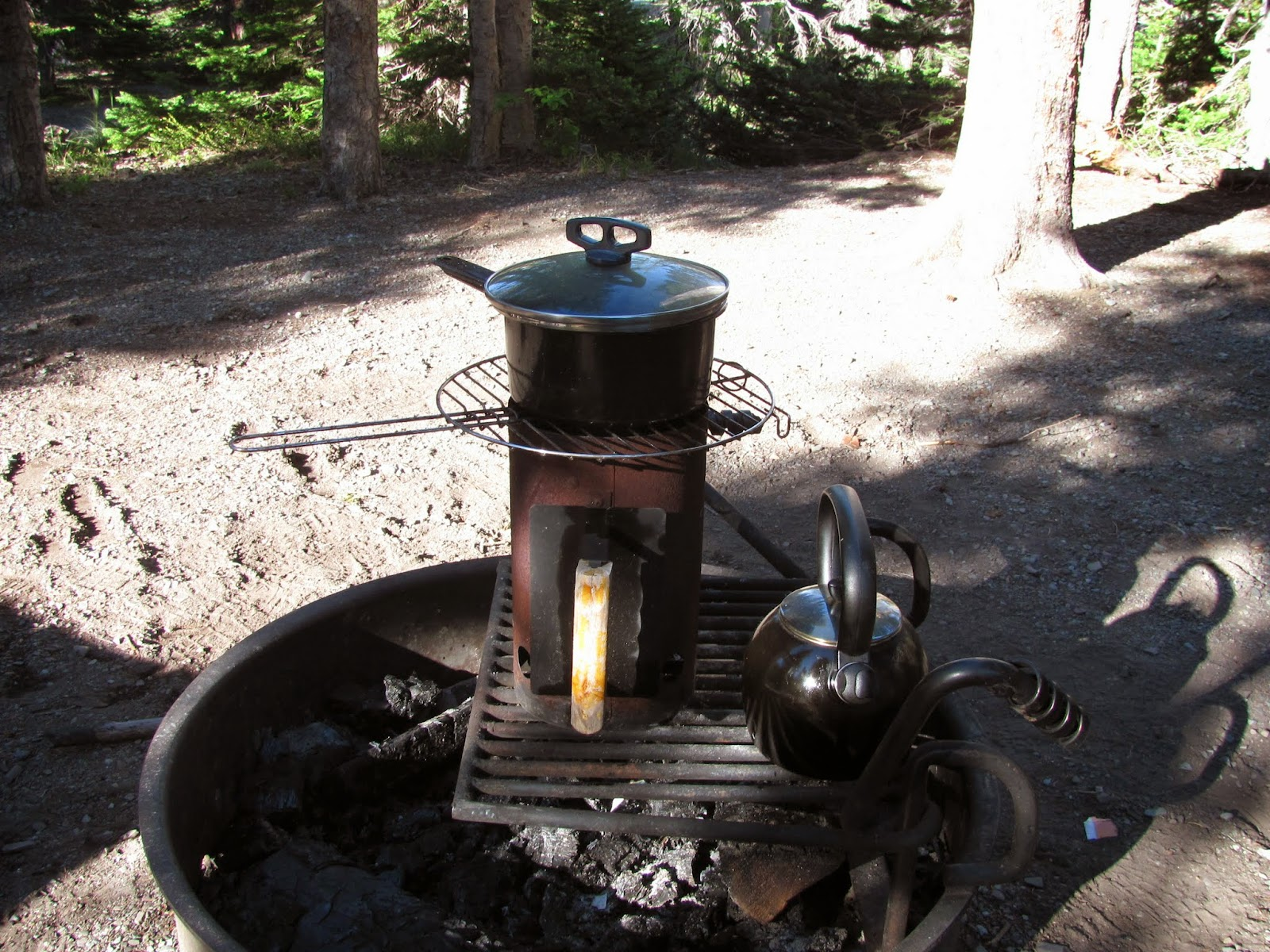 Cooking beans in the black pot over the charcoal chimney at Glacier National Park, Montana