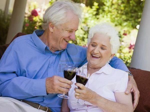 пожилая пара пьёт из бокалов и улыбается