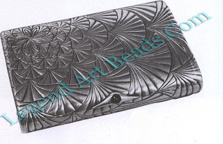 A rectangular silver cigarette case in the Art Nouveau style set with a sapphire push button.