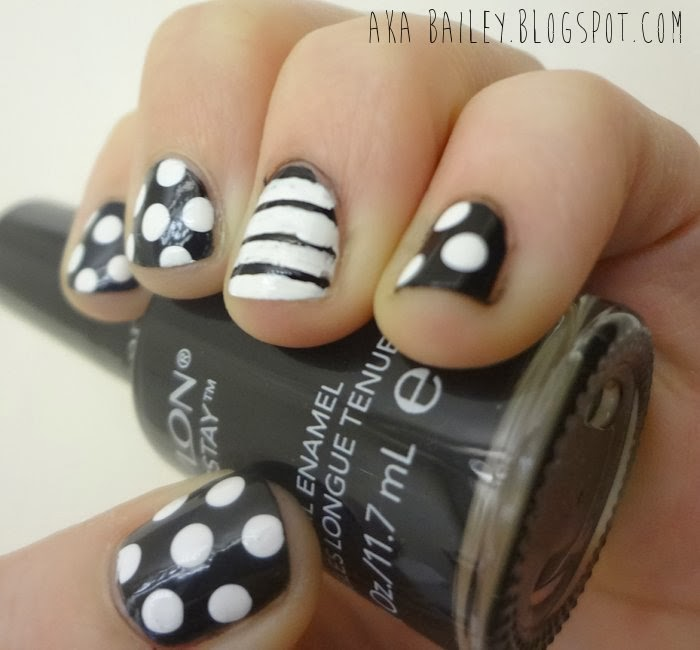 Black nails with white polka dots, white nail with black stripes as an accent nail