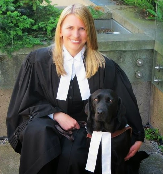 Carrie kneels down in her formal black Barrister's gown with a white long tie smiling next to her guide dog Casey (black Lab in harness also wearing a white long tie).